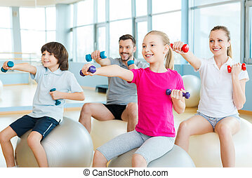 Exercising together is fun Happy sporty family exercising in...