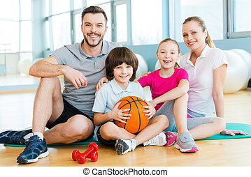 Happy to be a family. Happy sporty family bonding to each other while sitting on exercise mat together