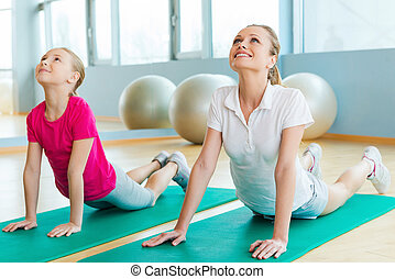 Warming up in sports club Cheerful mother and daughter doing...