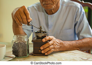 Asian senior man with vintage coffee grinder and coffee...