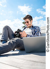 Young photographer with laptop and photo camera - Young...