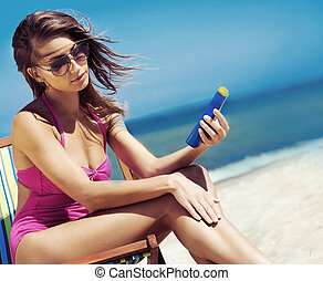 A young woman in a swimsuit adding suntan on the beach -...