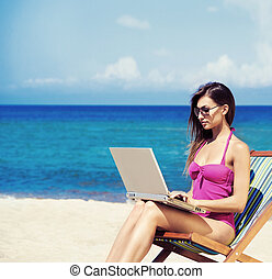 A young woman relaxing with a laptop on a beautiful beach -...