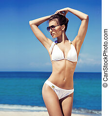 A beautiful woman in a swimsuit relaxing on the beach -...