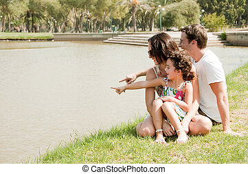 Family sitting near the lake
