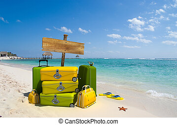tropical trip - luggage and sign on a beach resort