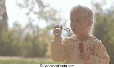 Little blonde girl blow bubbles on nature