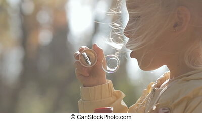 Close up of a little blonde girl blow bubbles in park