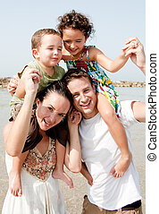 family in the beach - Parents with children sitting on the...
