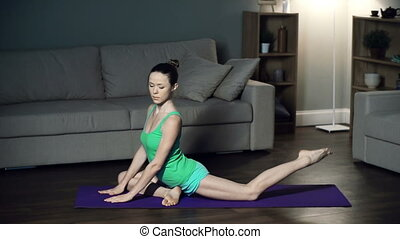 Pigeon Posture - Close up of woman practicing yoga at home...