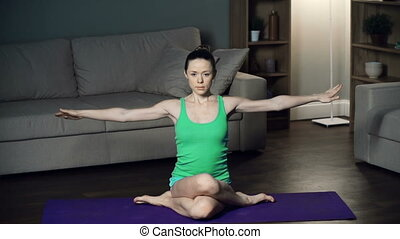 Cow Face Pose - Woman sitting on yoga mat with her knees...