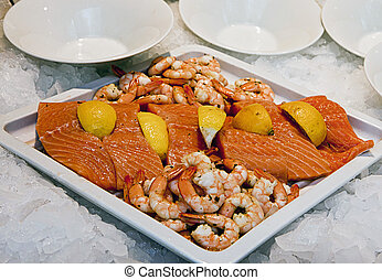Plate of raw salmon, shrimps and lemon slices on ice