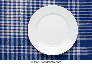 White classic plate on blue checkered tablecloth.