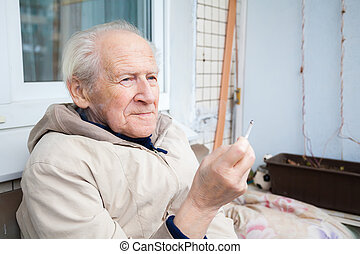 old man enjoying a cigarette - pensive old man enjoying a...