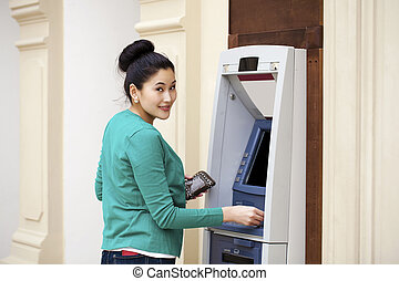 Asian lady using an automated teller machine . Woman...