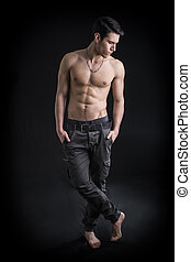Full length shot of handsome, fit shirtless young man...