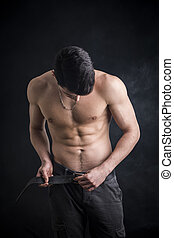 Handsome, fit shirtless young man undoing pants' belt to...
