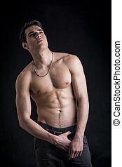 Handsome, fit shirtless young man wearing only pants,...