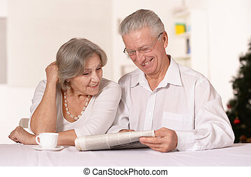Amusing old couple - Portrait of amusing old couple reading...