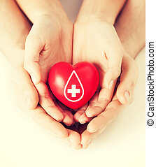 hands holding red heart with donor sign - healthcare,...