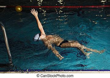Kid swimming backstroke - Kid in goggles swimming backstroke...