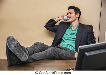 Smiling handsome young businessman at desk on phone