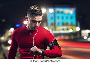 Jogging at night - Young sportsman jogging in the night city