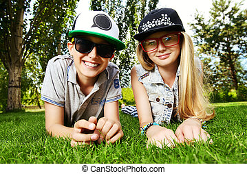 friends - Two cheerful teenagers on the grass in the park....