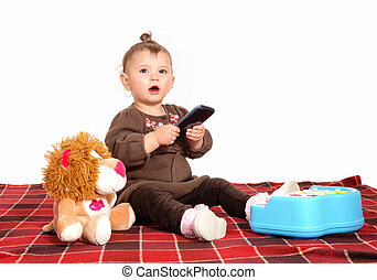 Baby playing with cell phone. - A little baby girl sitting...