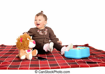 Baby having fun with her toys. - A little baby girl sitting...