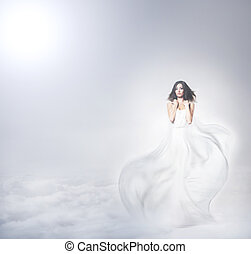 Young and beautiful angel woman in blowing dress over the...