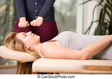Bioenergy therapy session - Young woman relaxing during...