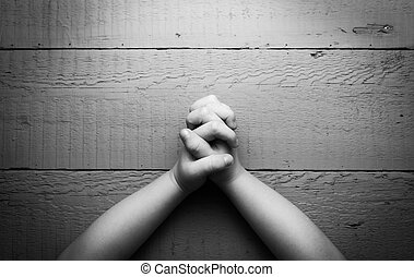 Child's hands folded together in prayer. Black and white...