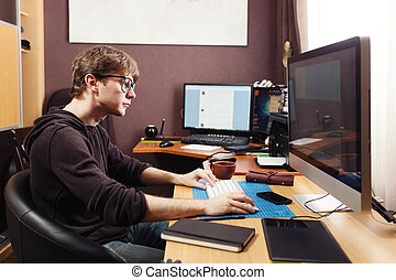 Freelance developer and designer working at home, man using...
