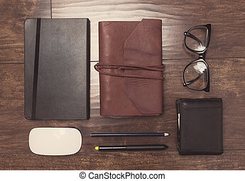 Notepads in leather cover with pencils and eyeglasses on wooden