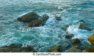 Evening landscape. The rocky coast of the ocean. Waves and...