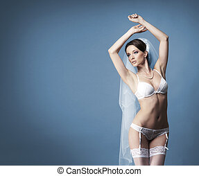 Young sexy bride in erotic lingerie over grey background -...