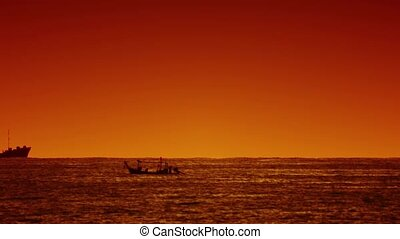 Big ship and small wooden boat in the sea at sunset