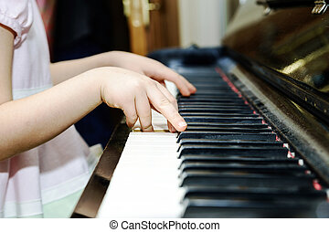 Girl's hands and piano keyboard close-up view, education...
