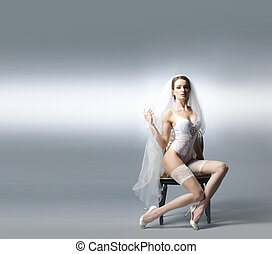 Young sexy bride in erotic lingerie over grey background...