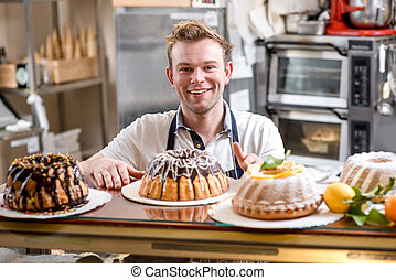 Man with Easter cakes - Handsome man in apron with Easter...