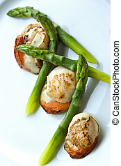 Gastronomic dish - Saint-Jacques and green asparagus on a...