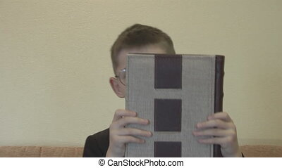 boy with glasses with a book imitates famous actor