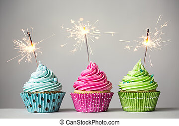 Three cupcakes with sparklers - Row of three cupcakes with...