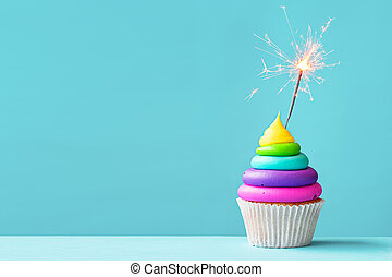 Colorful cupcake with sparkler - Brightly colored cupcake...