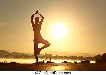 Silhouette of a fitness woman exercising yoga meditation...