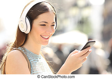 Woman listening music from a smart phone in the street -...