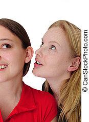 woman whispering in her friend�s ear