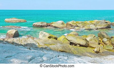 Tropical Sea Water Lapping Gently at Rocks at Low Tide -...