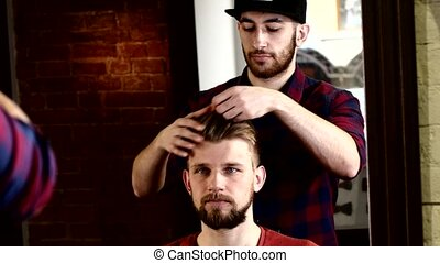 Master stylish men's barbershop shows work to client in the mirror. He was satisfied with his new look